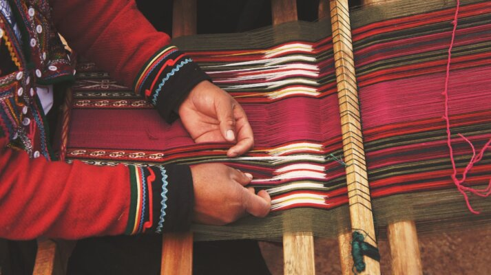 Mani intrecciano un tessuto su un telaio